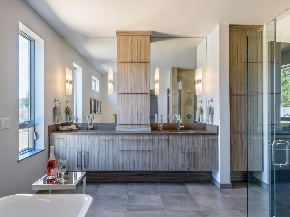 Large master bathroom featuring a rustic bathroom counter with two sinks and mirrors lighted by wall lights. There's a freestanding tub in front of the walk-in shower.