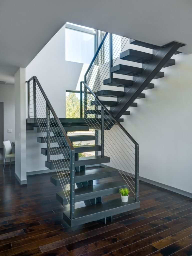 The open staircase design is compact, practical, and aesthetically pleasing, allowing the surrounding natural wood flooring to take precedence.