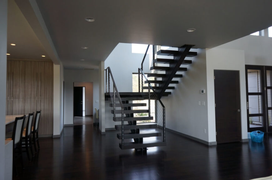 Framed in the sprawl of the open-plan space, the metallic stair structure makes for both a unique visual detail and unobtrusive access to the upper floor. Through the stair void, we can see plentiful natural light spilling in.