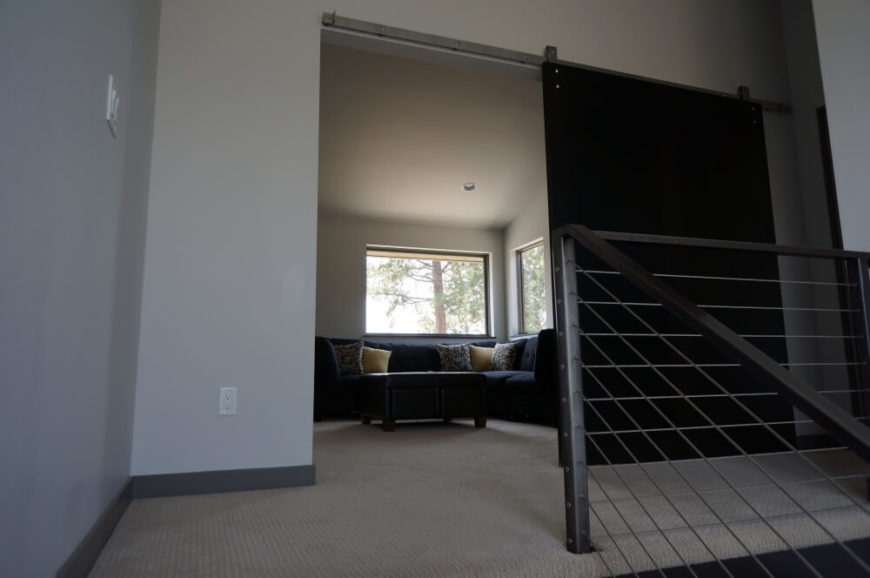 At the top of the stairs, we come to a more private relaxing space, parked behind a large sliding panel door. Large windows in this area enhance the airy style.