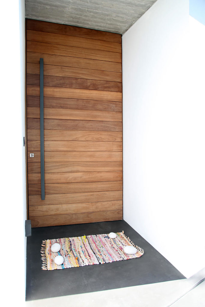 The modern styled wooden front door, with a charming and colorful rag rug, hides the entrance to the house. Nearly all the materials used in the house can be seen in this small alcove.