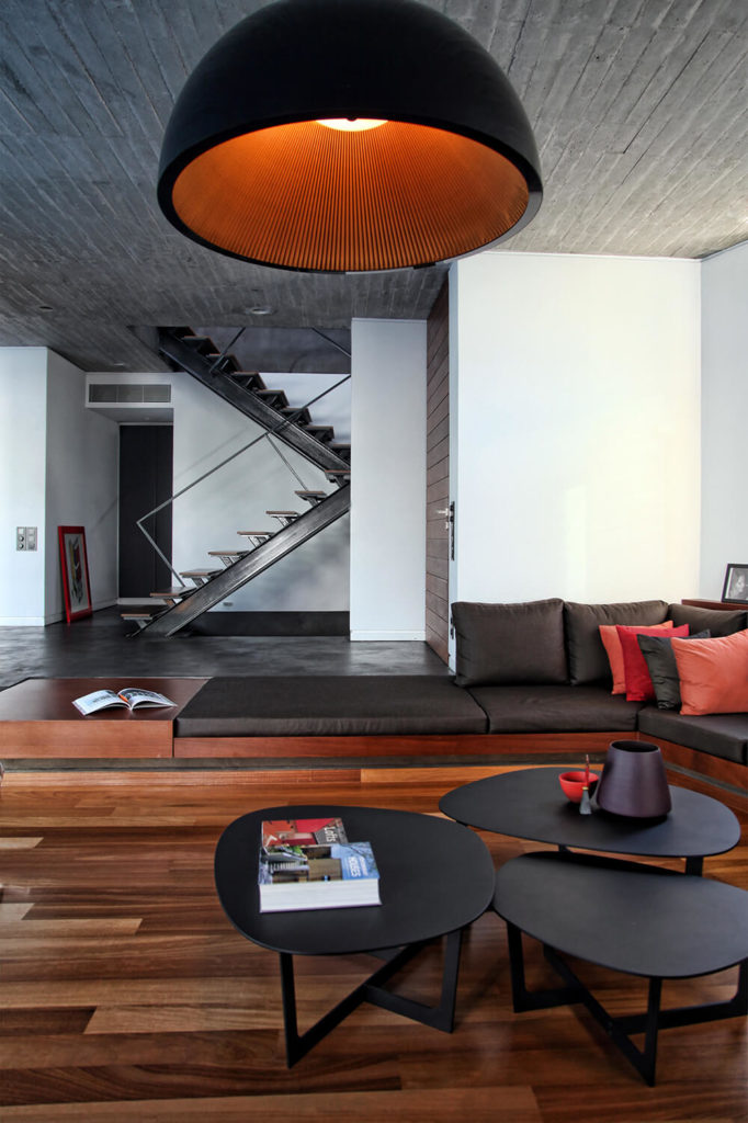 The white walls of the interior space allow the colors of the space to pop against the walls. This view of the inside of the house shows off the stairs leading up to the second level. Their industrial construction of steel beams and wood matching the living room floor brings the materials up into the rest of the house.