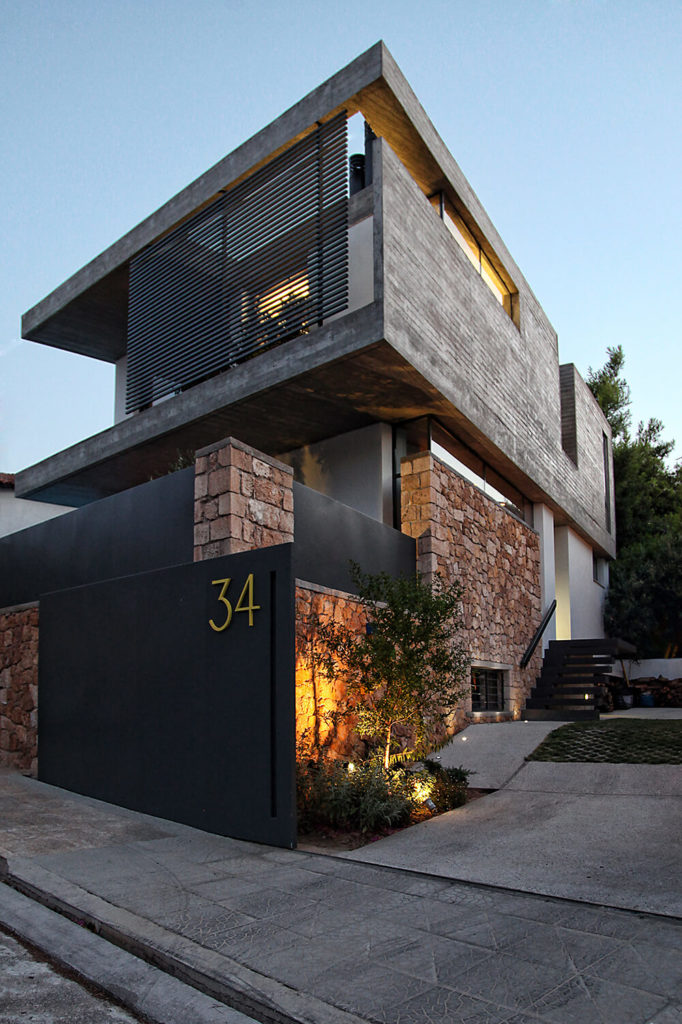 From the exterior, the three levels of this house create a striking visual against the surrounding backdrop. Stone walls crafted of locally sourced stones surround the house, allowing for privacy and creating great contrast against the exposed concrete and black walls used in the rest of the house design.