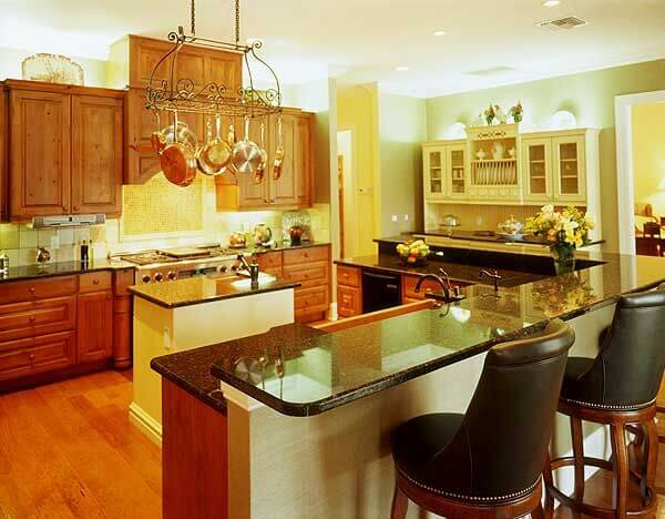 This more traditionally styled kitchen already has multiple countertops, including an L-shaped countertop and bar area. This kitchen already has so much countertop space that a large island isn't necessary or wise to add in. Instead, they put in a small island with a rinsing sink.
