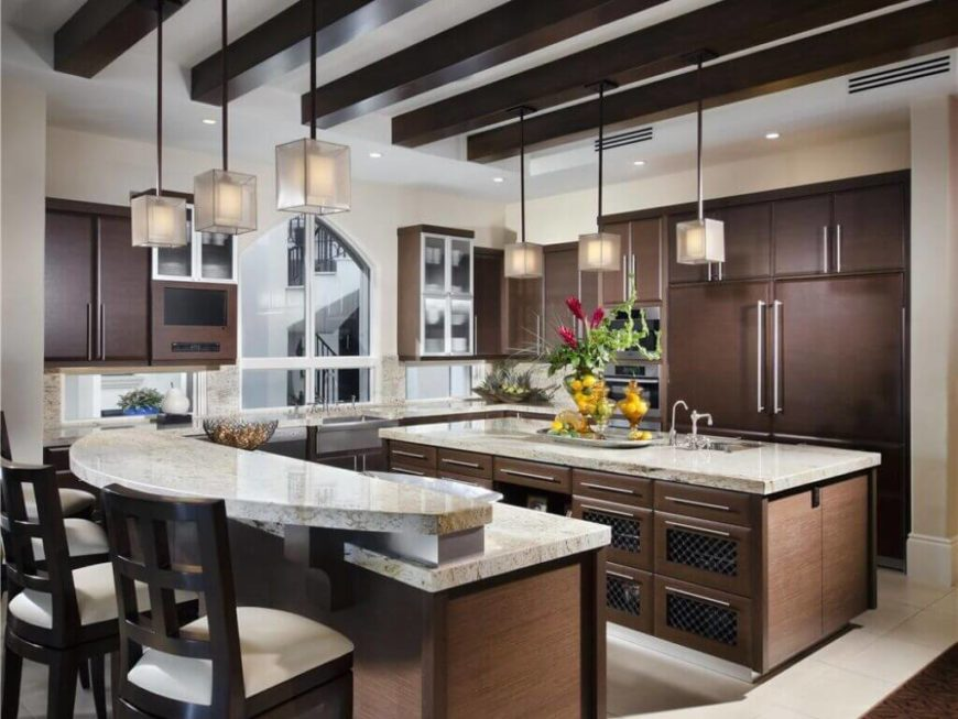 This is another enormous luxury kitchen that features two islands in addition to spacious countertops. One acts as a serving area and breakfast bar, while the other features a spacious sink area.