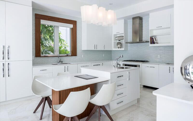 A white modern kitchen with a light gray glass mosaic tile backsplash and a small island that serves as a in-kitchen eating area and as extra countertop and storage space.
