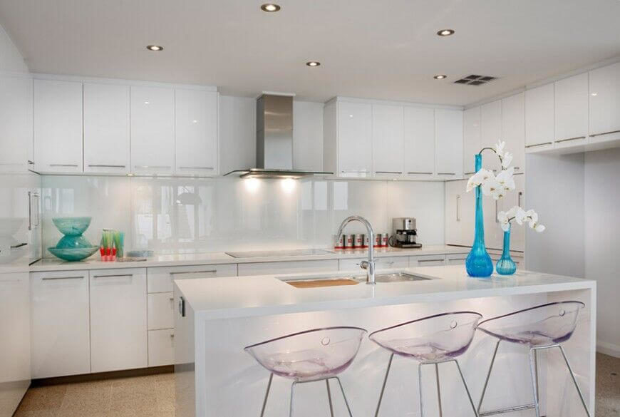 A minimalist white modern kitchen featuring a small white island with a dual basin sink and blue accent pieces.