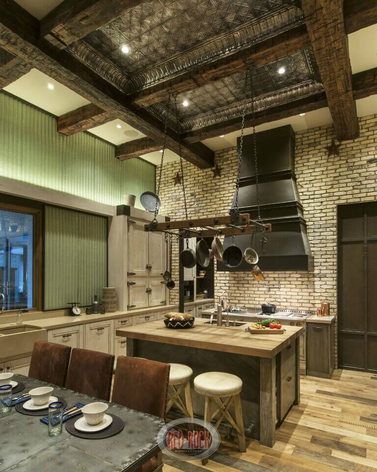A rustic stone and metal kitchen with a small wooden eat-in island with a pot rack above the preparation space and sink.