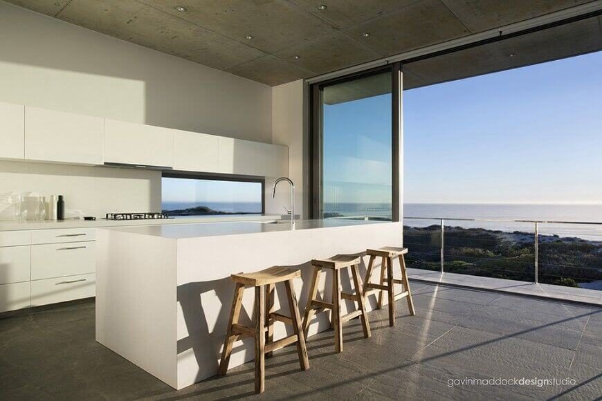 A minimalist kitchen with a single sink located in the massive white island. To the right are floor-to-ceiling pocket doors leading out onto the terrace with a great view.