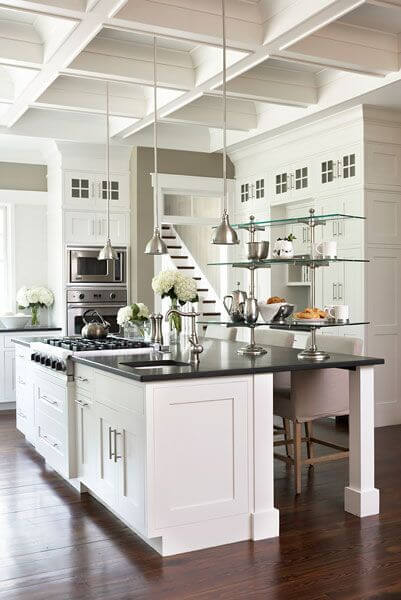 A black and white kitchen with glass shelving, pendant lights, and an  elegant coffered