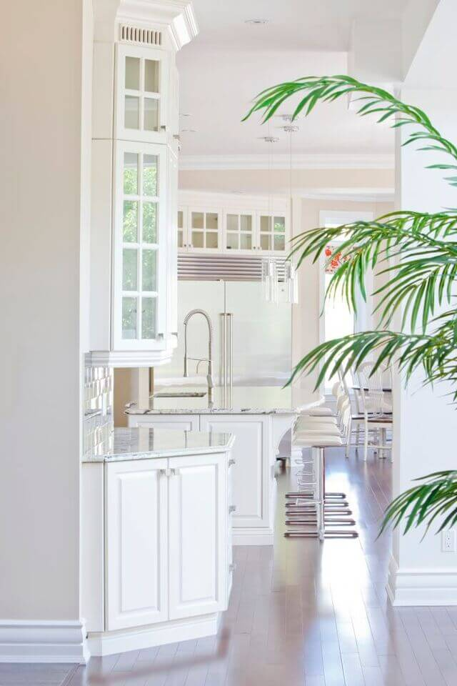 A brilliantly white kitchen with modern barstools and a luxurious sink set into the marble kitchen island.