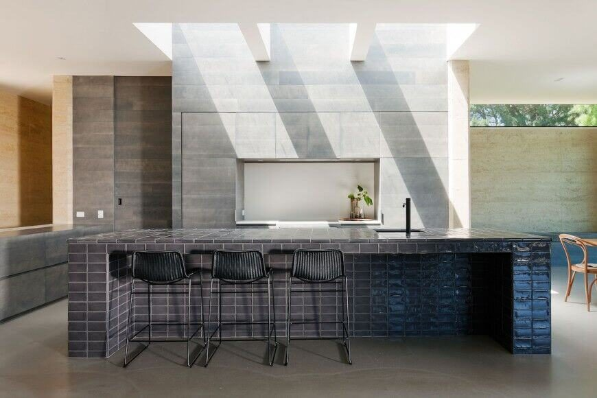 A unique kitchen design with a glass subway tile covered island with a spacious eating area in addition to a deep sink with modern fixtures.