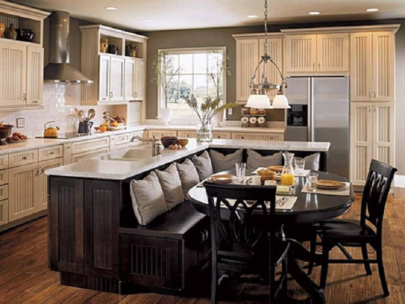 A lovely country kitchen featuring an L-shaped kitchen island that transitions into bench seating for the attached dining area. The island also includes a large farmhouse sink.