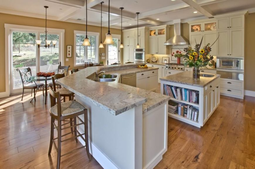 An incredibly spacious kitchen featuring hardwood flooring, granite countertops, and a small kitchen island with built-in cookbook storage and a small secondary sink closer to the stove.