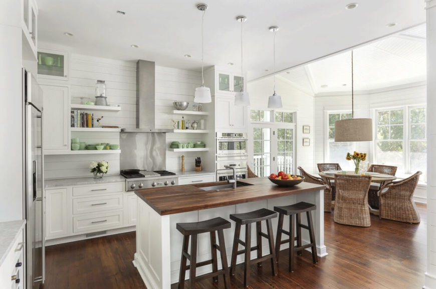 An elegant open-concept kitchen with an adjacent dining space, bay windows, and a single white island with butcher block countertops and a single basin stainless steel sink.