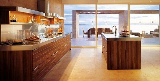 Without the wood and stainless steel island, this kitchen would feel utterly empty, with all the open space feeling wasted. Adding the island not only adds countertop space, it also fills the open kitchen, making it feel a bit more cozy, without interrupting the great beach view through the windows.