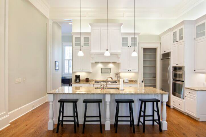 An all white kitchen with contrasting black barstools on one side of the lengthy white island with cream granite countertops.