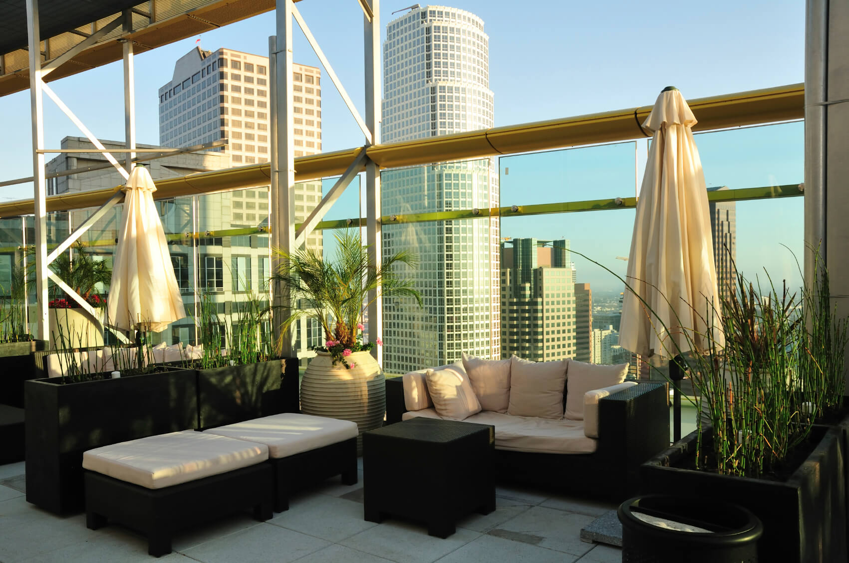 This incredible rooftop patio is enclosed by tall glass balustrades and completely covered by a tall roof. Intimate seating areas are each equipped with a sofa, several ottomans, a coffee table, umbrella, and divided by tall planters with grasses.