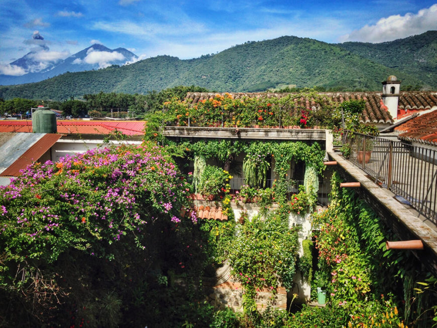 Climbing vines and draping bushes fill this courtyard and rooftop with beautiful greenery and flowers. The space is teeming with gorgeous life to break up the structure of this villa and highlight the surrounding mountains.