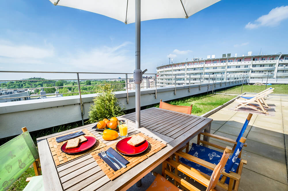 A lovely, large rooftop patio with sunny fabric colored chairs, a large table complete with a parasol, and a grass rim all around the stone patio.