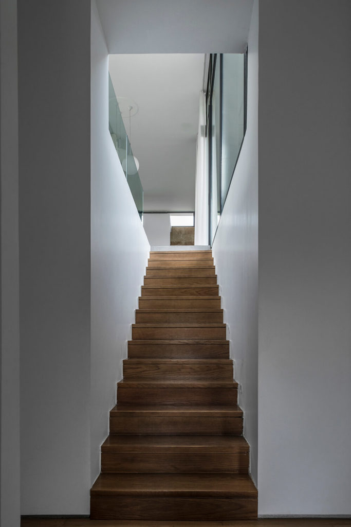 An entrance from the lower level opens up to immediately reveal this wooden staircase. This small entryway features plain white walls with little decoration.