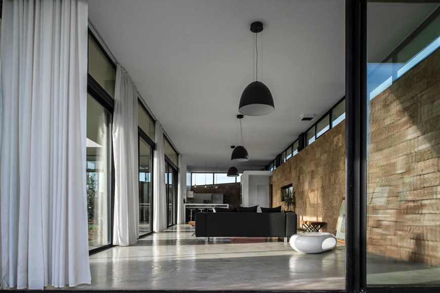 An open sliding door reveals the interior of the upper level, and you will see a large living space. The large pendant lighting matches the furniture, and the brick wall opposite of the windows is the back bone upon which the room was built.