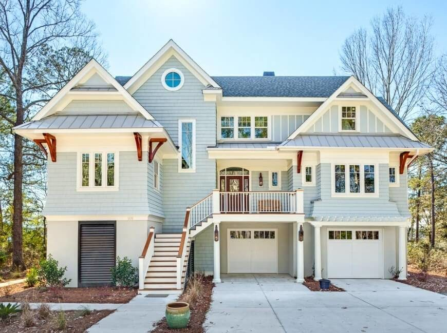 this combination of shingles and board and batten with the white and redwood accents creates a
