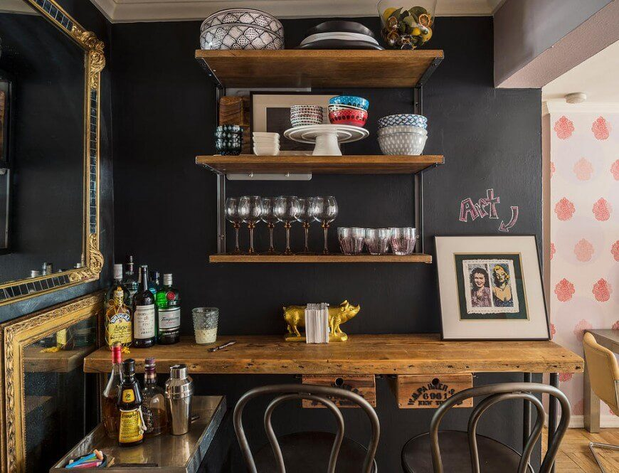 In this kitchen, there is a mini bar featured with an eat-in counter standing before a chalkboard wall. The natural wood shelving compliments the chalkboard and works well with the dark colors. Mirrors are featured on the wall to the side, which can help to give the room more depth.
