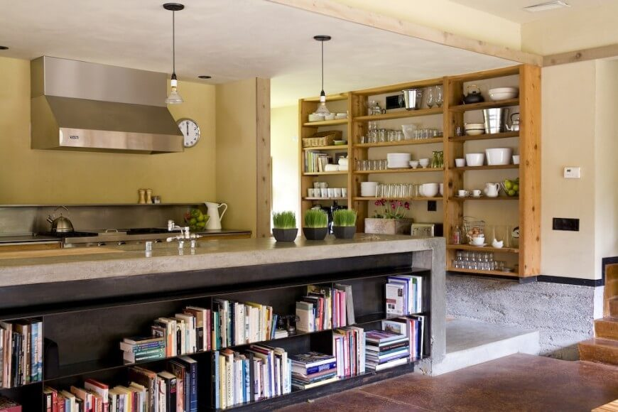 Multiple shelving units provide plenty of storage space for this kitchen. The large countertop features a bookshelf below it, and offers plenty of space for working or eating. The shelving unit mounted to the wall is made up of a stained wood and provides a perfect place to store kitchen supplies.