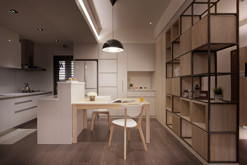 A modern kitchen equipped with a large shelving unit featuring staggered shelves and boxes for storage. Soft wood grain is an ongoing theme in this space, and it is complimented by soft lighting above the dining table.