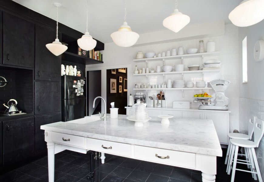 This white saturated kitchen is boldly contrasted by a pitch black wall and floor. Pendant lights hang throughout the space, and light the space well. The large island table provides plenty of space to eat and work, complete with a large sink.