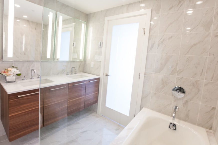 In the master bathroom, we see a broad double vanity through the glass bath enclosure. The door features smoked glass to allow for both privacy and natural light.