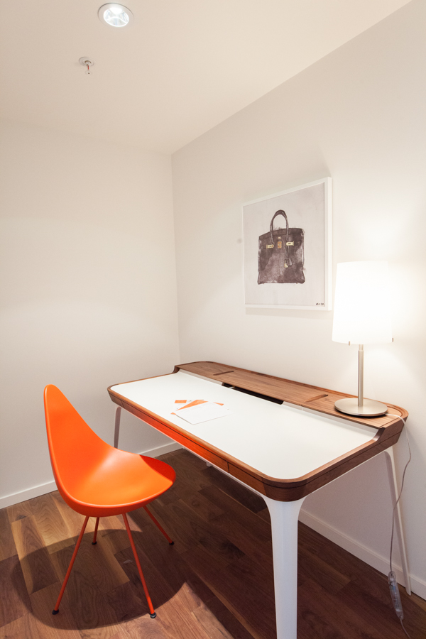 This home office space holds a truly unique modern design desk with a sleek mixture of glossy whites and natural wood. A bold orange chair stands in high contrast.