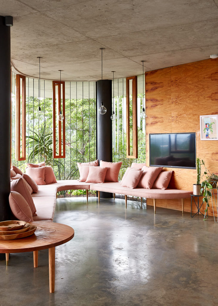 This bespoke living room space features a custom sectional in light salmon color, wrapping around the curved shape of the room and hugging the glass facade. Natural wood appears everywhere, including the accent wall holding the television.