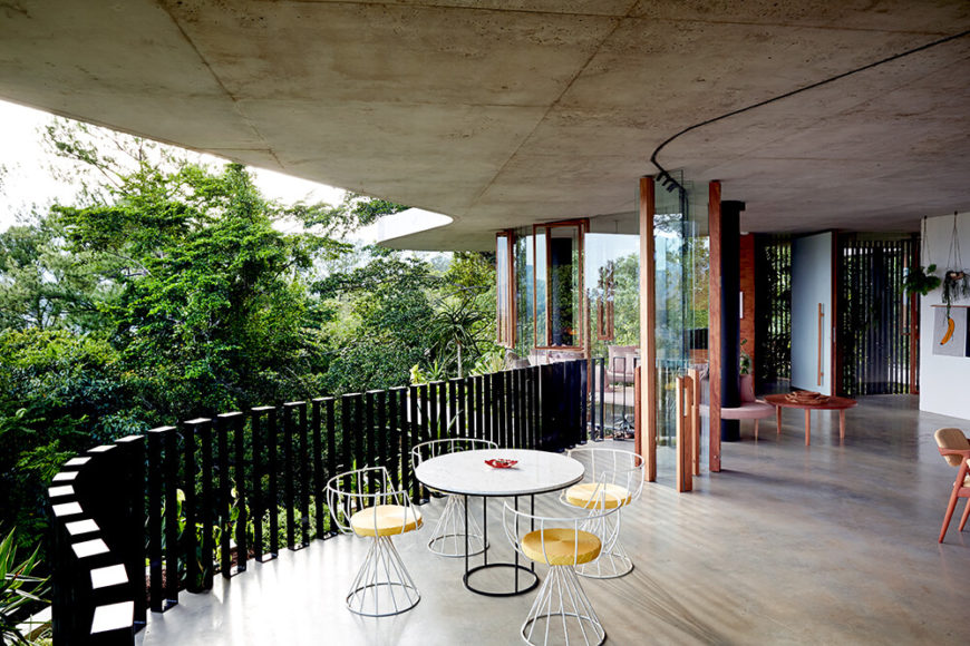 One of the most interesting facets of the design is how the wraparound glass panels can be folded away, completely erasing the line between indoors and out. The patio extension of the flooring holds a light wire frame dining set beneath the broad roof overhang.