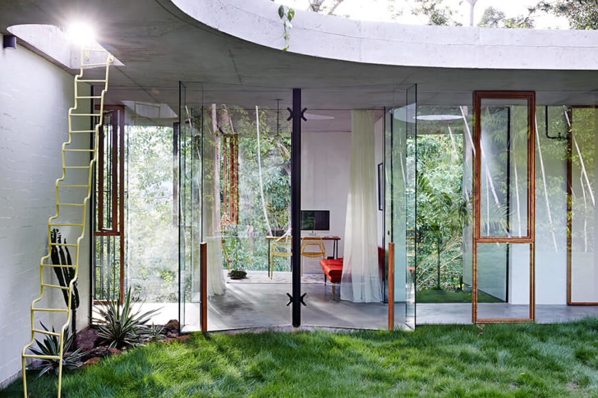 Just like the upper floor with its balcony, the lower floor opens directly to the outdoors via sets of glass panels. With a lush lawn bumping up against the exterior, the rooms feel even closer to nature.