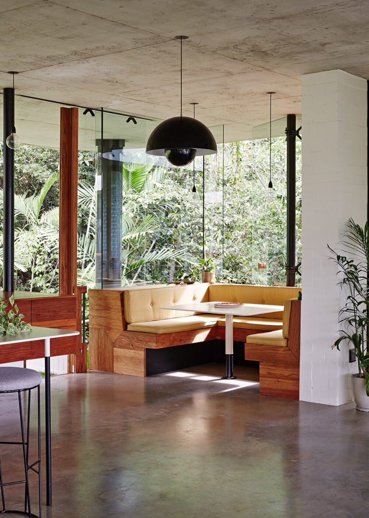 In a corner framed entirely in glass, a rich wooden breakfast nook warms the space. The natural materials create a great contrast with the bright white walls and concrete flooring.