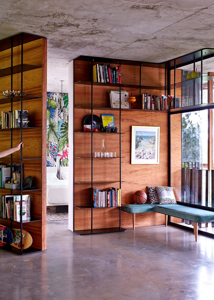 The unique wall here opens to reveal a bedroom, completely hidden from the main open plan area of the home. The built-in shelving serves a dual purpose, offering utility and a handle for opening the secret doorway.