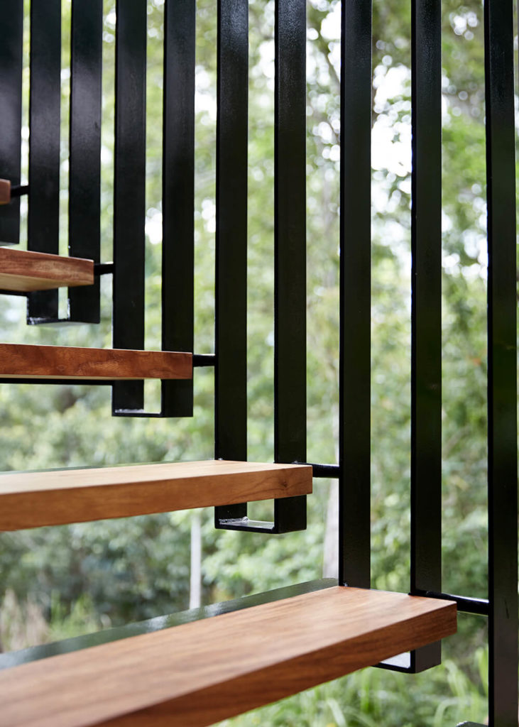 Here's a close detail of the hanging metal staircase that connects the upper and lower halves in the courtyard. Sleek hardwood steps combine for a high contrast, modern look.