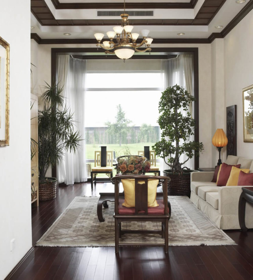 Oriental touches in the room are enhanced by the inclusion of the chosen house plants. The rich burgundy and gold accent colors bring out the gorgeous red hue of the wood floor and matching furniture.