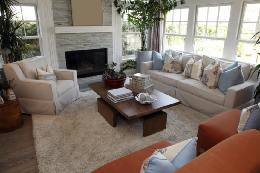 House plants add to the calm atmosphere of this peaceful room. Contemporary furniture paired with the layered stone fireplace and muted wood floors solidifies the design of the space. Burnt orange accents in the pillows and the two side chairs create interest in a neutral palette.