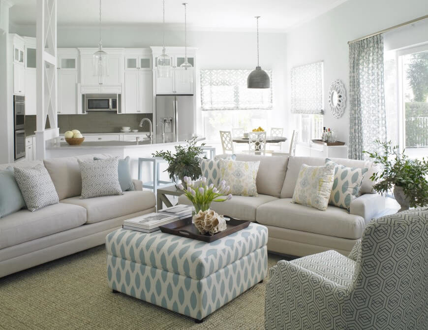 Against so much white and pastel blue, the greenery of the plant life pops into the foreground of the room. Delicate touches of yellow can be seen in the pillows and throughout the space.