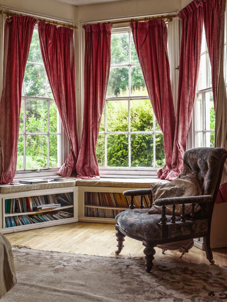 This home library boasts French windows overlooking the pretty outdoor views. The windows offer red window curtains.
