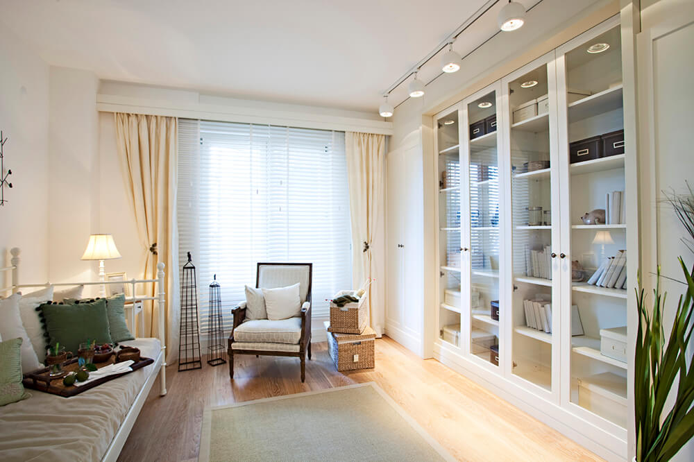 This chic bedroom offers white multiple bookshelves protected by glass doors lighted by track lights.