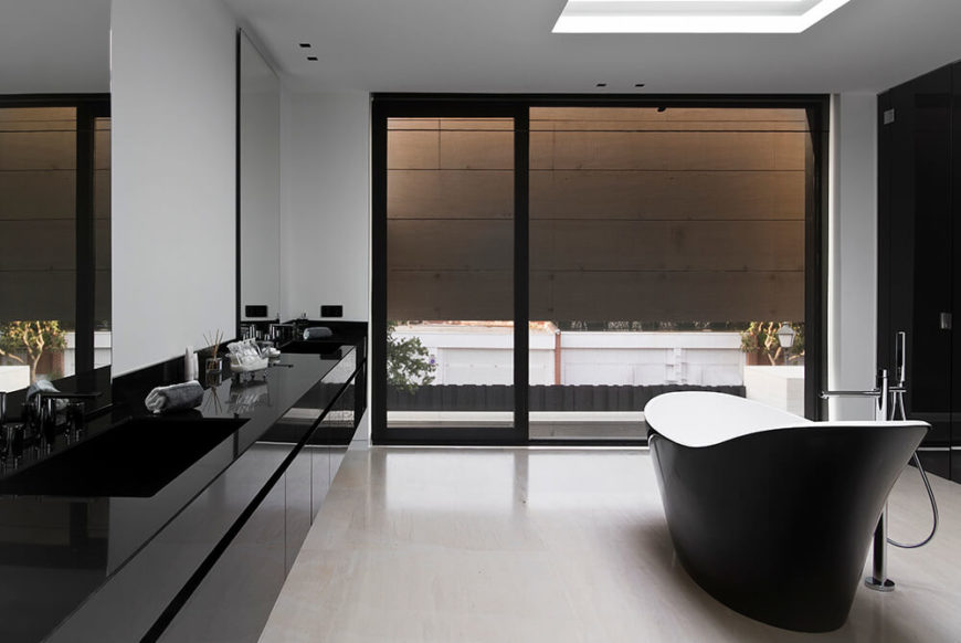 The bathroom is as immaculately designed as every other aspect of the home, flush with the high contrast look of black and white surfaces over a marble floor. The large sliding glass door leads onto the balcony, with a privacy wall wrapping around.