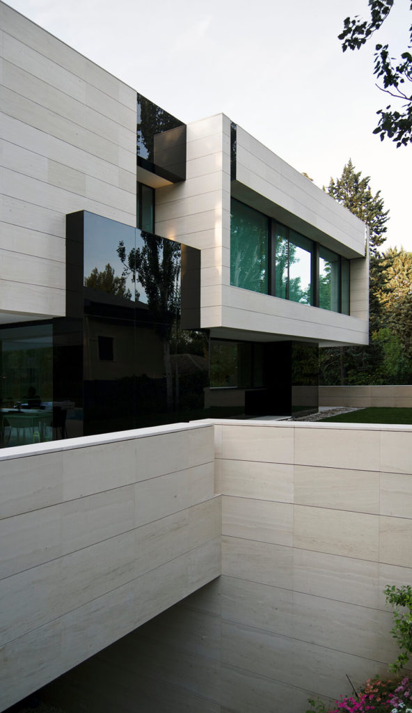 Overlooking the sloped void to the basement level, we can see the sleek black glass that acts as a counterpoint to the limestone on the facade. The deep, glossy voids supplement the reflective windows and add a sense of dynamism to the home.