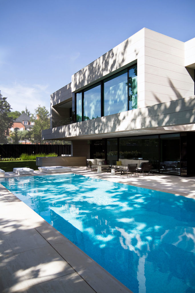 The exquisite pool sits neatly in the minimalist patio space, reflecting the modern charm of the home as well as the home itself in its glass flat surface.