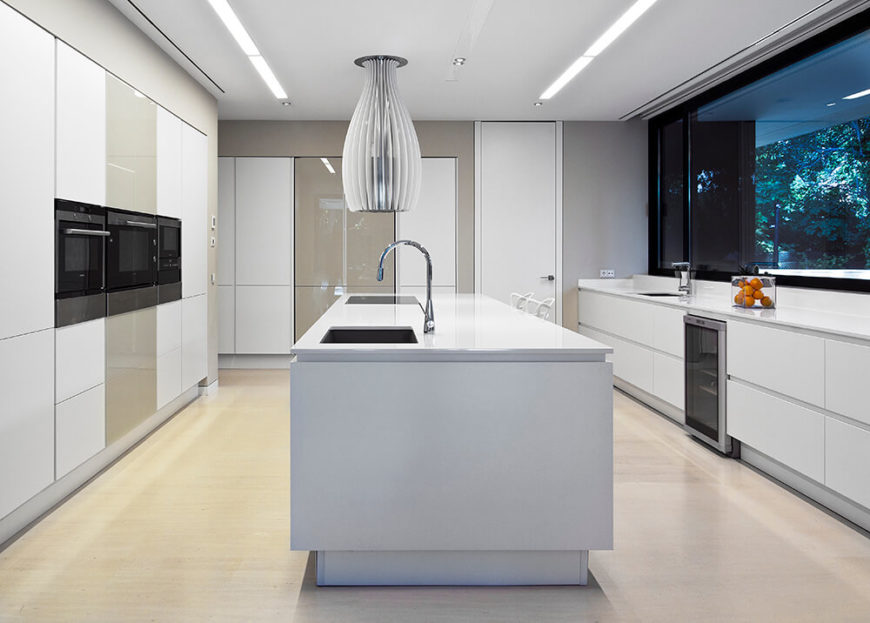 The kitchen is an immaculate, clean cut space flush with hardware-less cabinetry and glossy white surfaces. The large island features a built-in range and sink.
