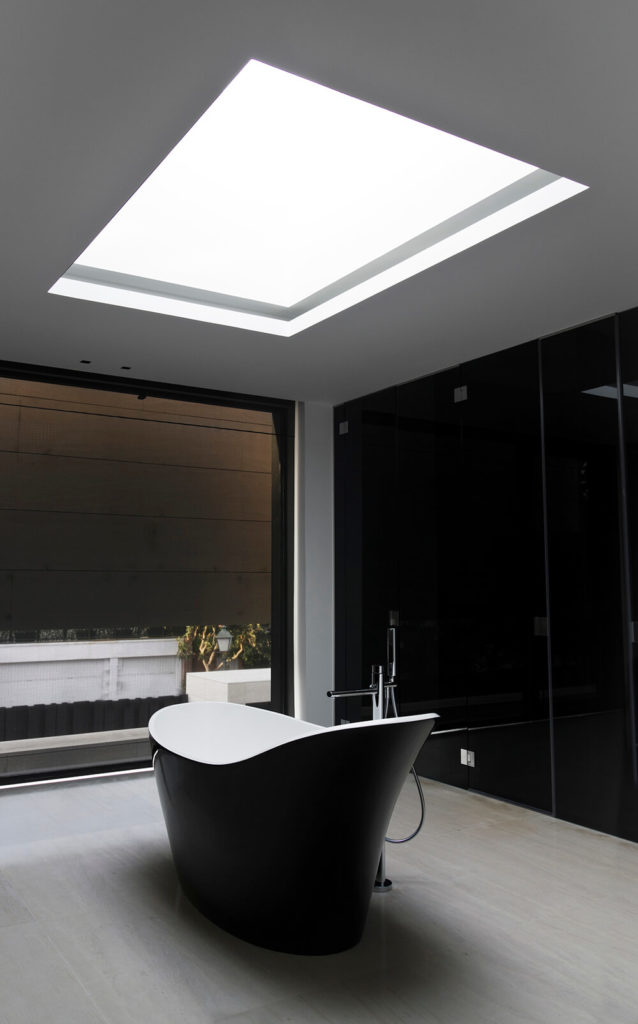 A massive skylight hangs above the soaking tub, which is filled by a chromed floor mounted faucet.