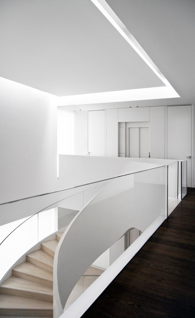 From the upper floor hallway, we see through glass balustrades down into the lower levels, with the curving staircase at center.